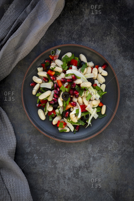 Plate of cannellini bean salad with fennel- bell pepper- black olives- pomegranate seeds- mint and parsley