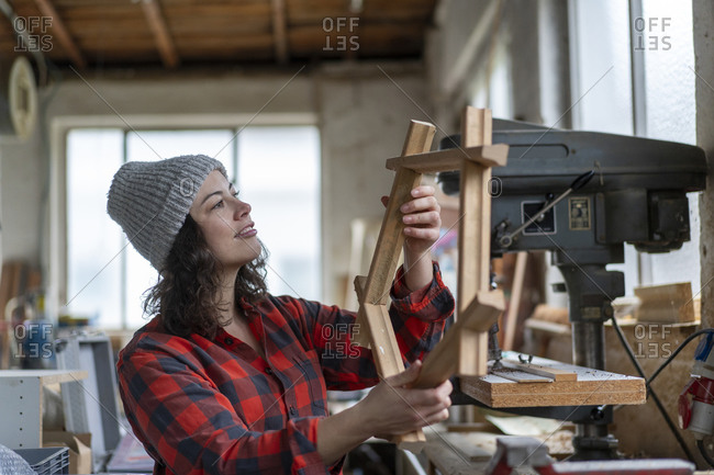 Carpenter holding workpiece in her workshop