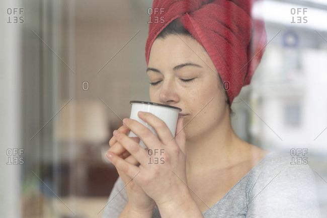 Portrait of woman with head wrapped in a towel drinking a coffee behind windowpane