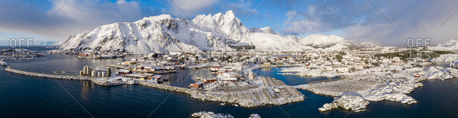 Norway- Ballstad- Aerial panorama of fishing village on shore of Vestvagoya island with mountains in background