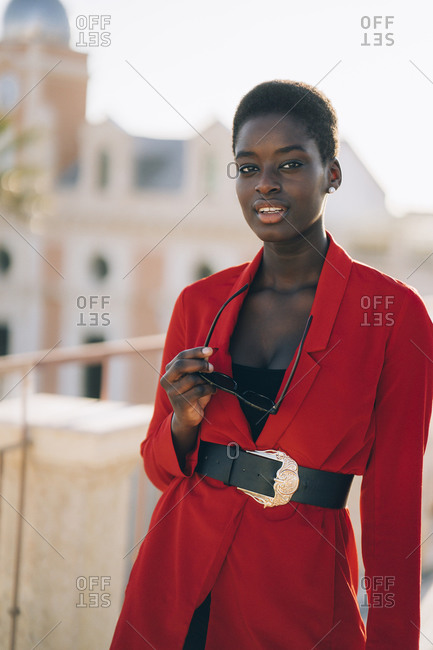 Young woman wearing red blazer and holding sunglasses