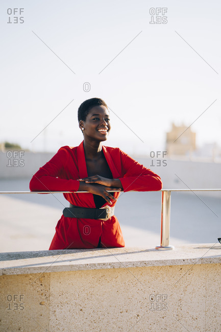 Young smiling woman wearing red blazer and enjoying view