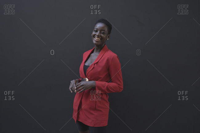 Young woman wearing red blazer in front of a grey wall