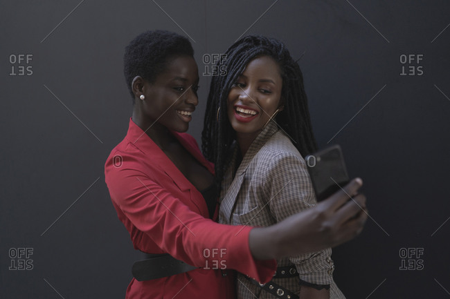 Two women taking a selfie in front of grey wall