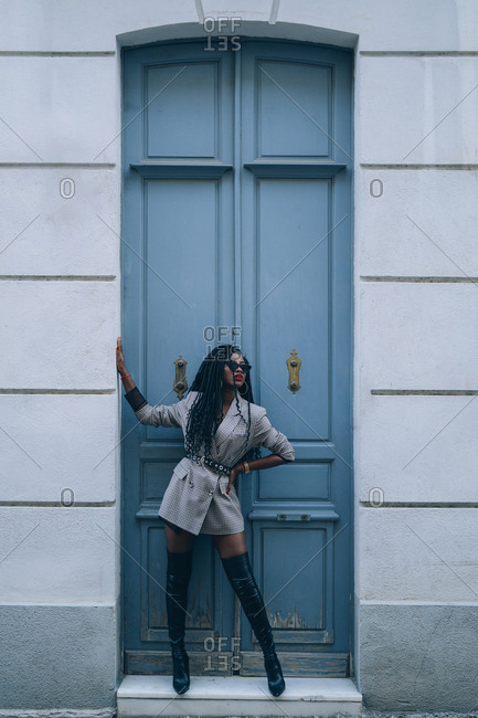 Young woman wearing grey blazer in front of a blue door