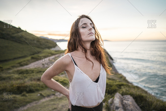 Red-haired woman with closed eyes standing on viewpoint at sunset