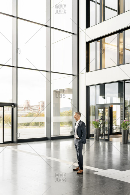 Successful businessman standing in entrance hall of office building- with hands in pockets