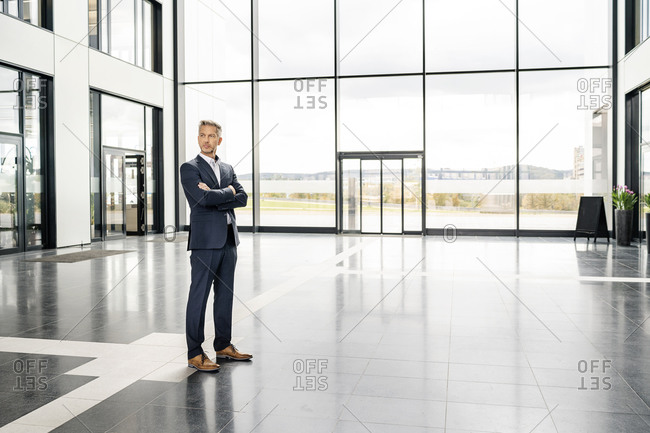 Successful businessman standing in entrance hall of office building- with arms crossed