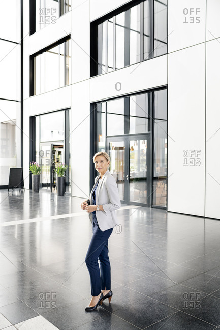 Successful businesswoman standing in entrance hall of office building