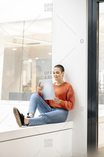 Relaxed businesswoman sitting on windowsill in office building- using digital tablet