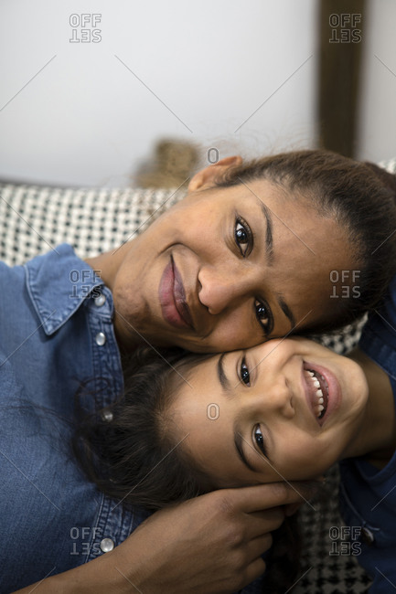 Portrait of happy mother head to head with her little daughter