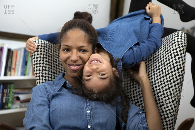 Portrait of happy mother head to head with her little daughter at home