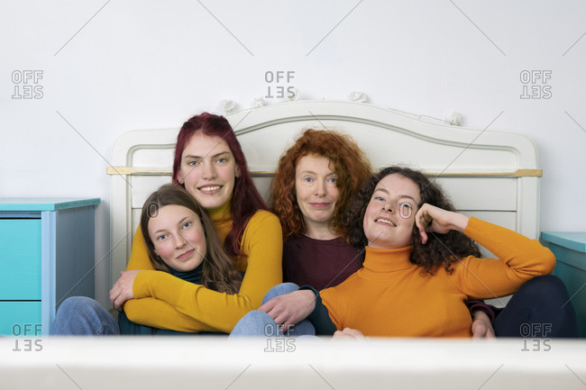 Portrait of mother and her three daughters sitting together on bed