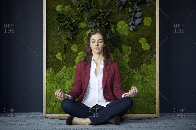 Businesswoman sitting on the floor in green office practicing yoga