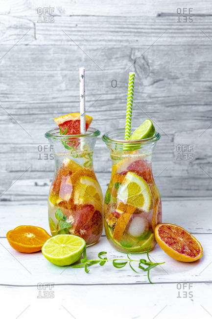 Jars of infused water with various citrus fruits- mint and rosemary