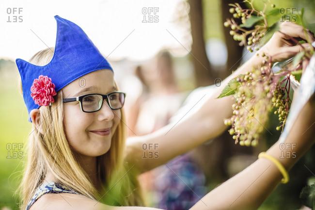 Girl wearing a party hat picking elderberries in garden