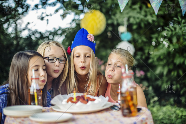 Girls having a birthday party outdoors blowing out candles on cake