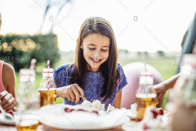Happy girl eating piece of cake on a birthday party outdoors