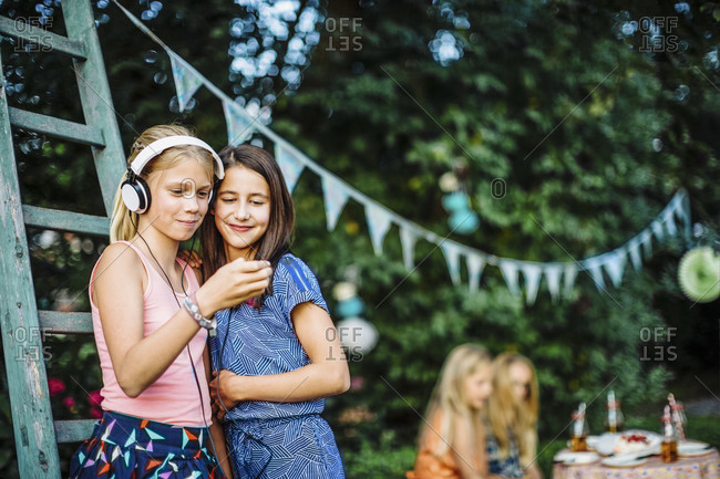Smiling girls with headphones and cell phone on a birthday party outdoors
