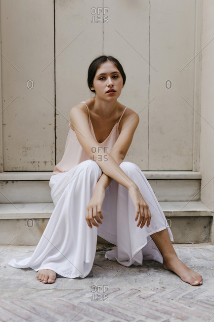 Portrait of barefoot teenage girl wearing white culottes sitting on steps outdoors