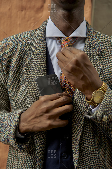 Close-up of stylish young businessman fixing his tie