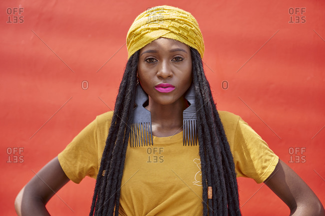 Portrait of woman in a long dreadlocks in front of a red wall