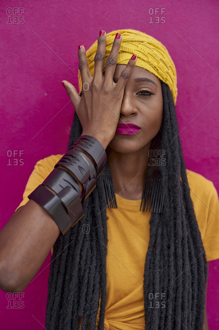 Portrait of woman with long dreadlocks covering her eye with one hand on a pink wall