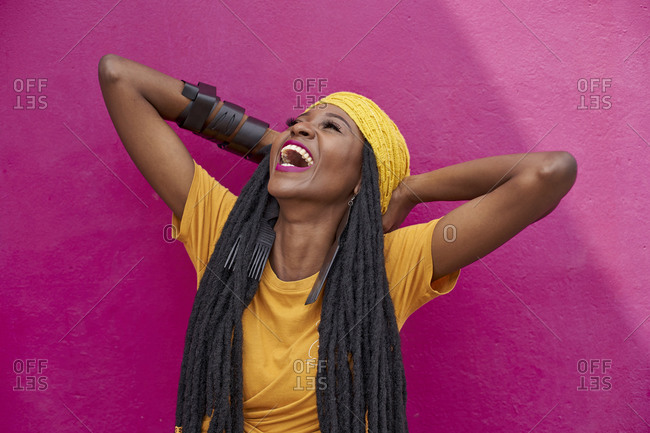 Portrait of woman with long dreadlocks laughing in front of a pink wall
