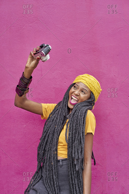 Portrait of woman with long dreadlocks taking a selfie with her camera in front of a pink wall