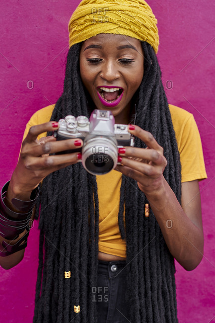 Portrait of woman with long dreadlocks in front of a pink wall