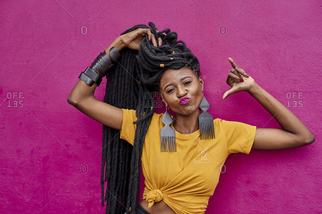 Portrait of woman with long dreadlocks making shaka sign in front of a pink wall