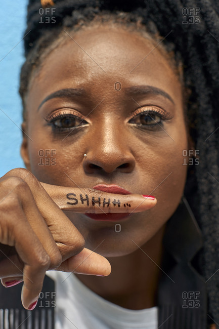 Portrait of woman doing the silence sign with her finger and a Shhhh message on it
