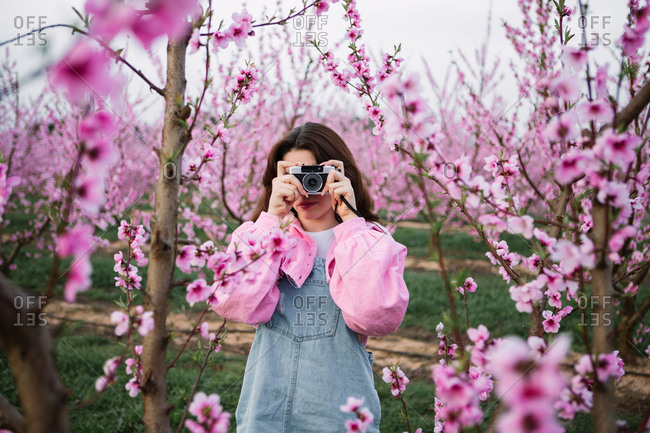 Fashionable young girl taking photos of blossoming fruit trees with a retro camera in spring