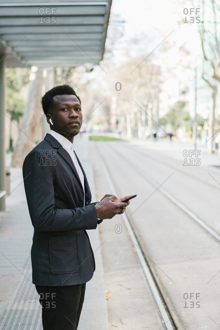 Young African entrepreneur in a suite is waiting for the tram at the station while using his mobile device in the morning