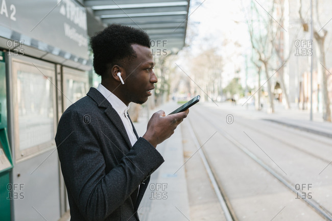 Young black entrepreneur is sending a voice message with his phone while waiting for public transport