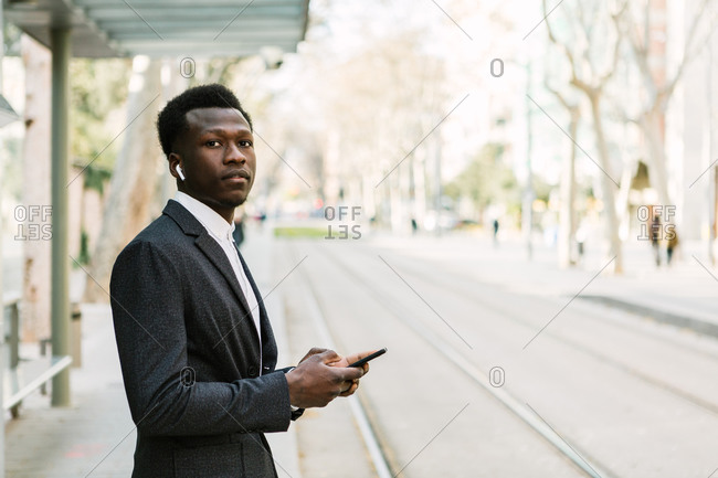 Young black businessman listening to music with wireless headphones and using his phone while waiting for the train