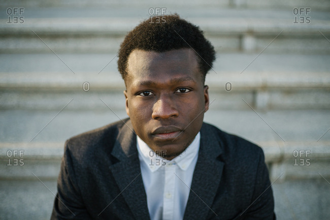Portrait of a black man wearing a suit sitting on the street