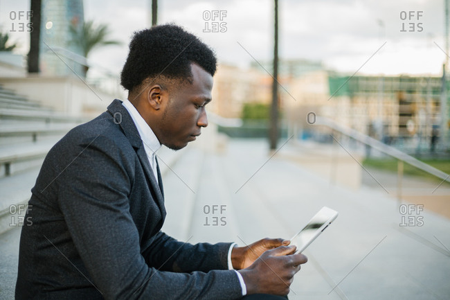 Side view of a young American worker in a suite using a tablet and reading the news on the street