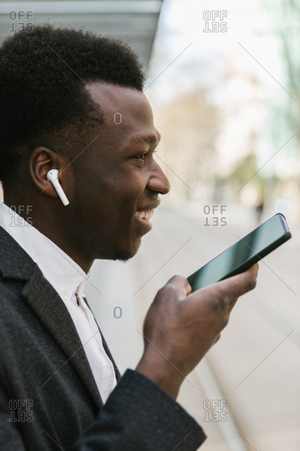 Side view of a smiling young black entrepreneur sending a voice message with his phone on the street