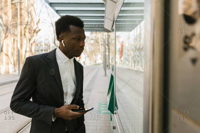 Black young man checking train schedules while listening to a podcast in his phone