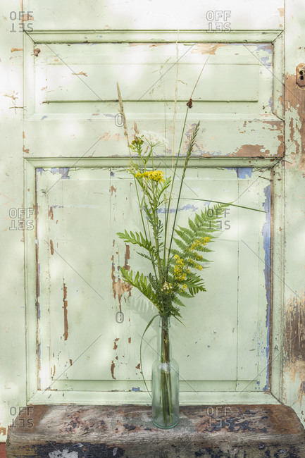 Yellow and green flower stems in vase by door with chipped paint
