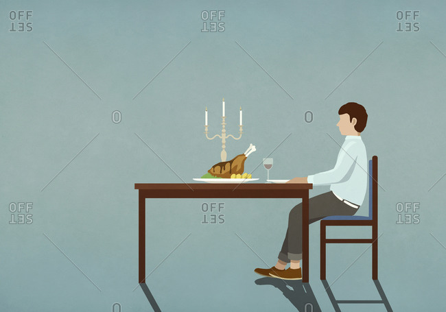 Man enjoying candlelight dinner alone at table