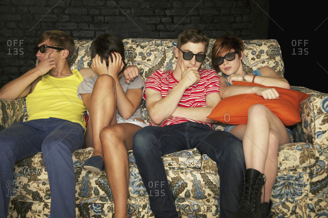 Cool teenage couples in sunglasses sitting on sofa at party