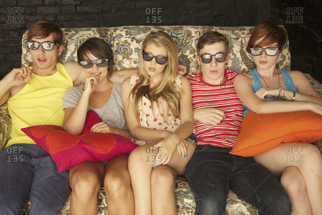 Portrait cool teenagers in sunglasses on sofa at party