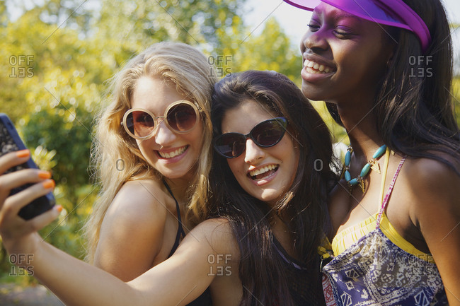 Happy teenage girl friends taking selfie with smart phone on sunny patio