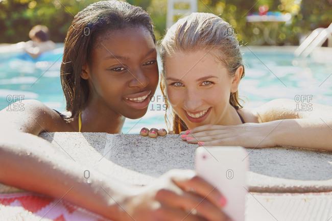 Teenage girl friends taking selfie with smart phone in summer swimming pool