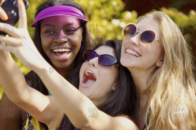 Happy teenage girl friends with sunglasses taking selfie