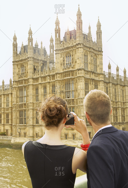 Young couple with camera photographing Houses of Parliament, London, UK
