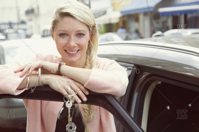 Portrait happy young woman with car keys standing in car door