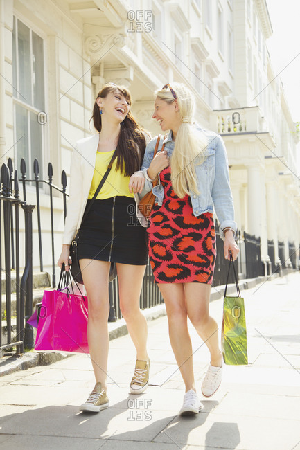 Happy young women friends walking arm in arm with shopping bags